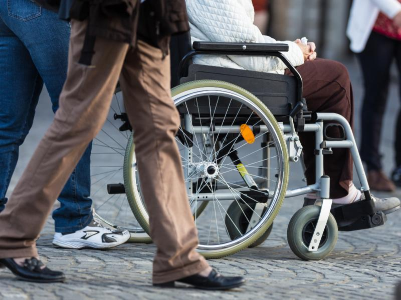 A lady in a wheelchair is being pushed by a companion in the street