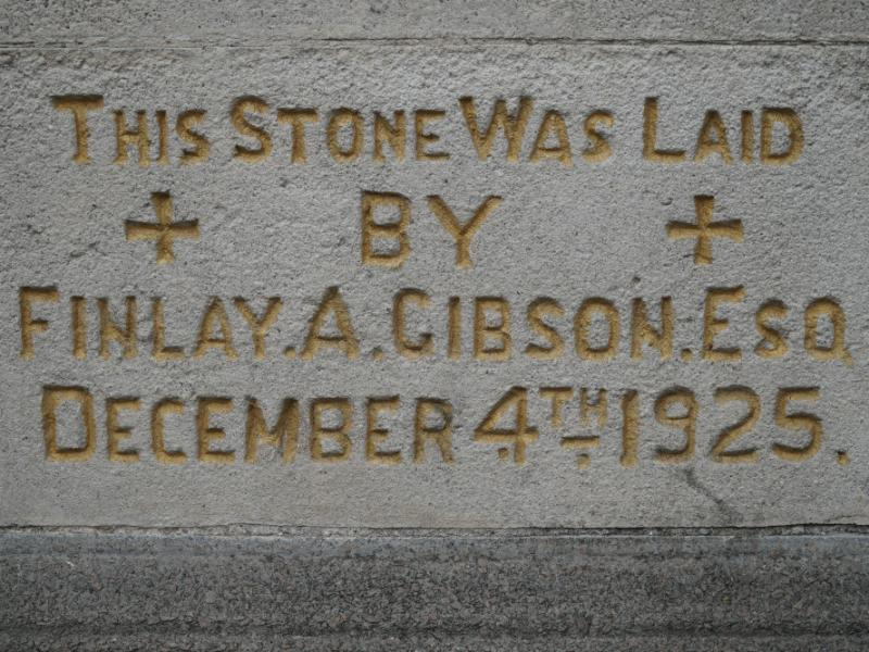 A close-up of a an engraved stone that reads The stone was laid by Finlay A Gibson Esq December 4th 1925