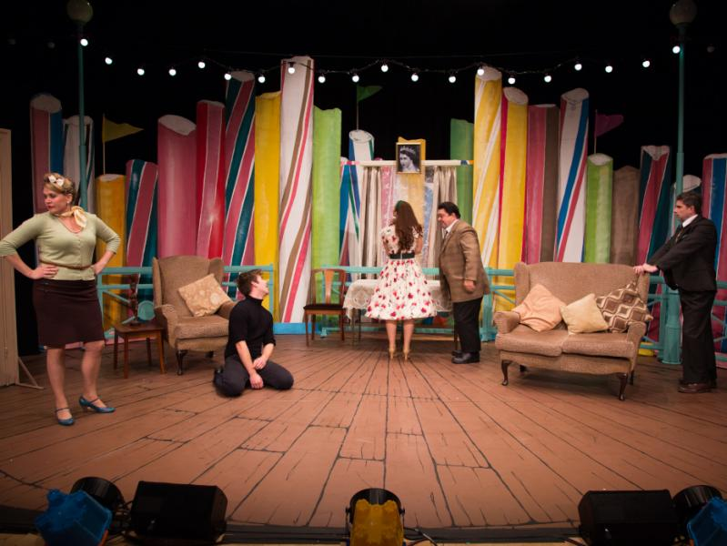 Five actors performing a scene from One Man Two Guvnors. The set is comprised of large sticks of rock.