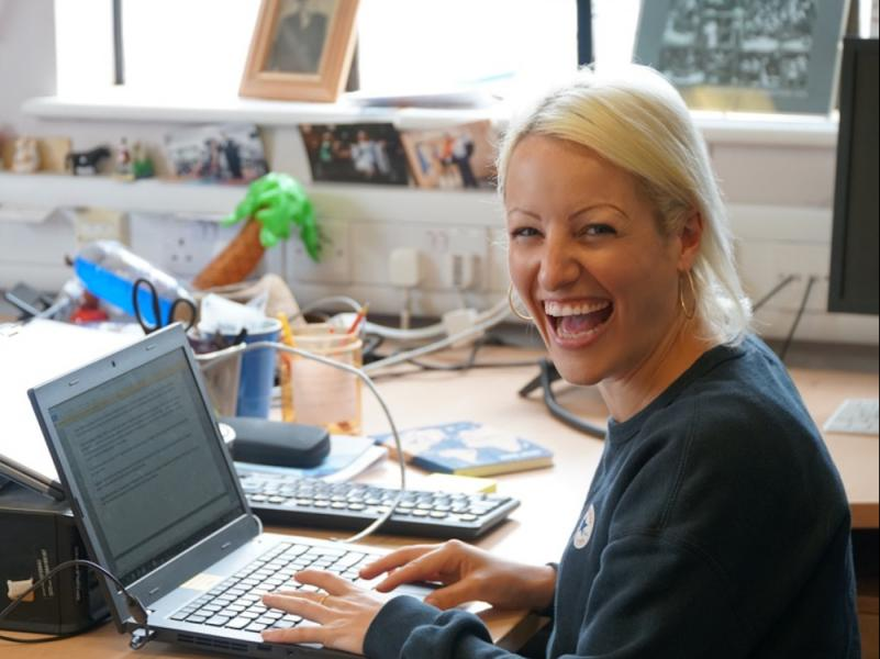 One of the Arts Development Officers (Beth Ryland) sits's in front of a laptop computer. She is facing the camera and smiling.