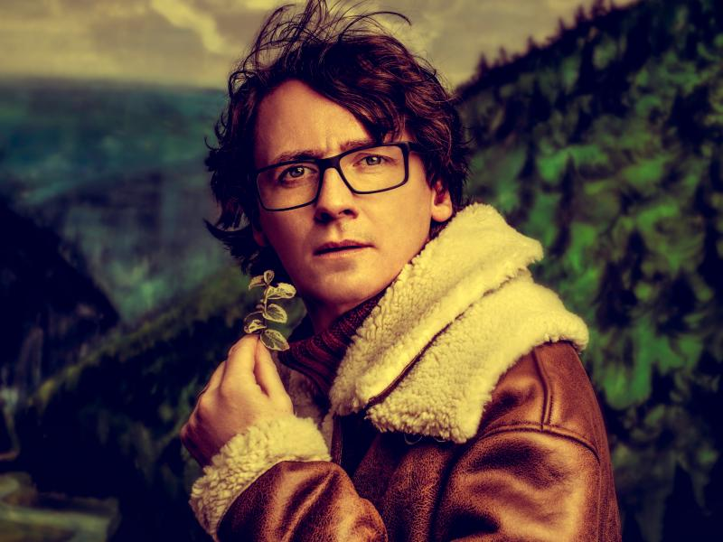 An image of Ed Byrne with a mountain and trees in the background. He is wearing a brown leather jacket with fur collar and cuffs, and a red roll-neck jumper. He is holding a leafy plant.