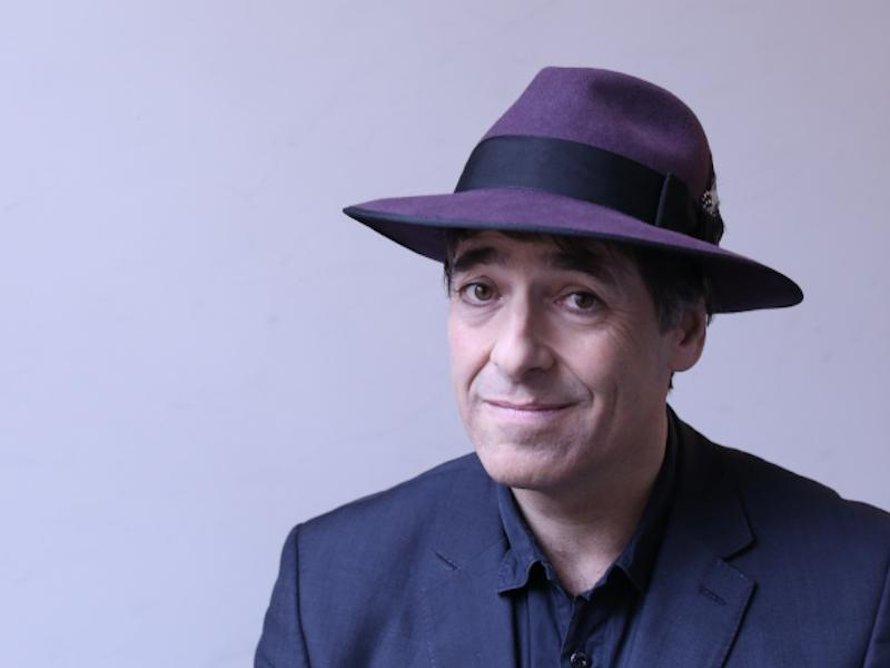 A photograph of Mark Steel on a lilac background. He is wearing a navy suit and a purple and navy hat.