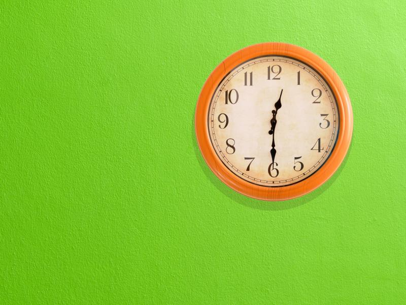 An analogue wall clock that reads 12.30. There is an orange frame, white face and it's on a green wall.