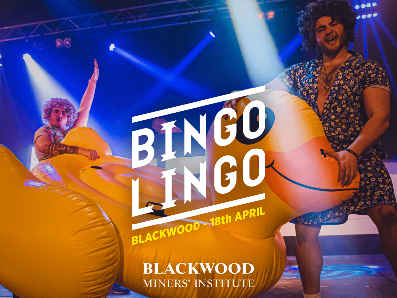 Two men in wigs and dresses are holding a large yellow rubber duck. There are spotlights pointing at them. The text on the image reads Bingo Lingo, Blackwood - 18th April, Blackwood Miners' Institute