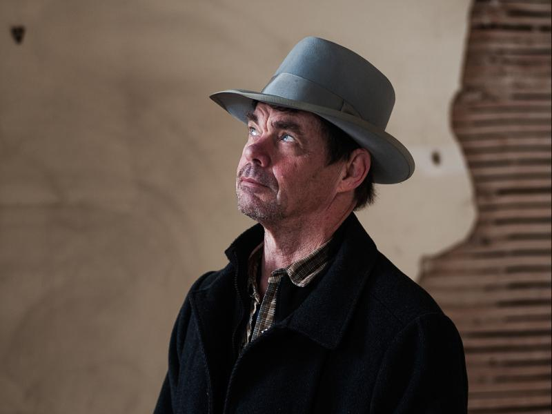 A photograph by Roddy Hand of Rich Hall. He wears a black coat and a grey hat and is looking up.  Behind him is a brown and beige wall.