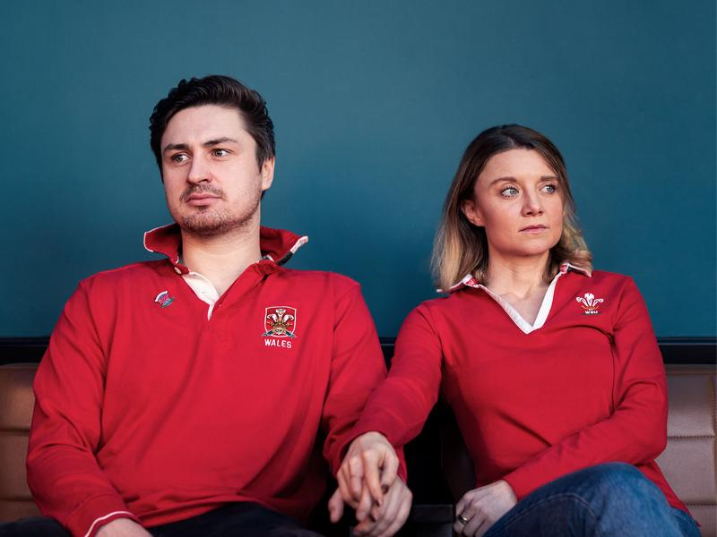 A couple sit together, both wearing Welsh rugby jerseys.  They are holding hands but they are looking in opposite directions