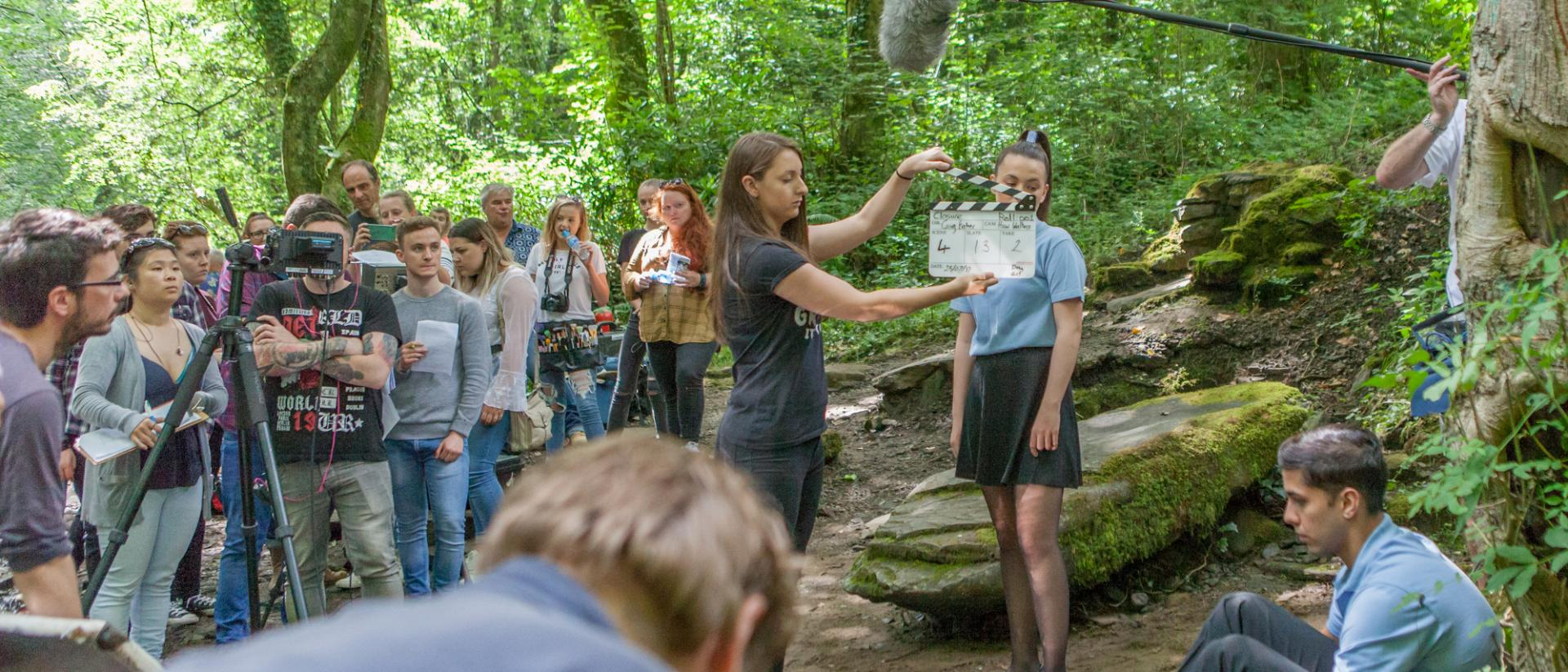A group of teenagers are in a forest. They are congregating behind a large video camera. One young lady is in front of the camera holding a film clapper board.