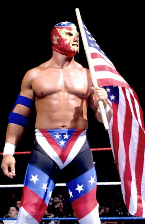 A photograph of a wrestler waving an American flag and wearing a mask and shorts. He is in a wrestling ring with an audience behind him.
