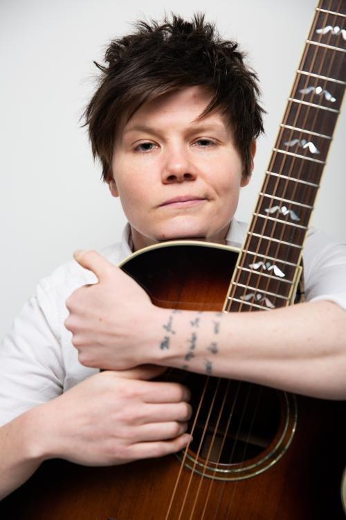 A close up of the singer-songwriter Grace Petrie. Grace has short dark hair and is wearing a white T-shirt. She is hugging an acoustic guitar.